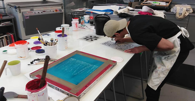 a man leabing over a desk at a screen printing workshop
