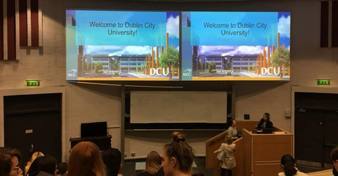 """Screens in a lecture theatre which read """"Welcome to Dublin City University"""""""