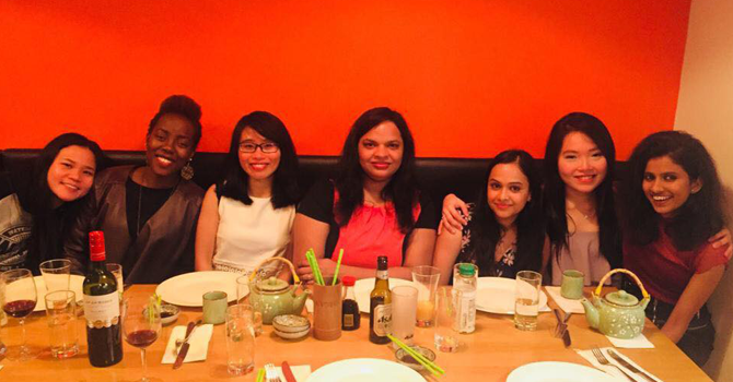 7 women sit at table after finishing dinner, smiling to camera