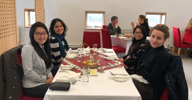 Four women sit a table having lunch