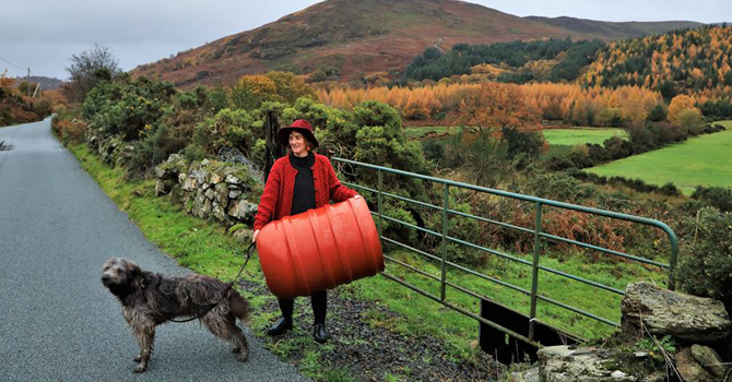 A woman in a red coat and hat stands on a country road with a dog, with a mountain in the background