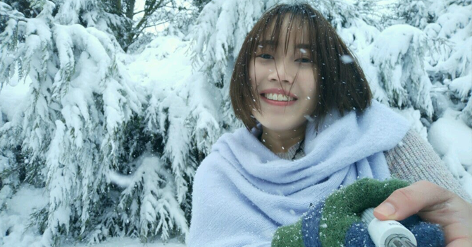 Student wrapped in big scarf smiling in front of snowy backdrop