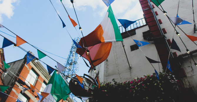 Irish flags attached to bunting in front of a clear sky