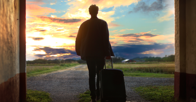 Image of a person's back walking away from camera, into the sunset and pulling a small suitcase