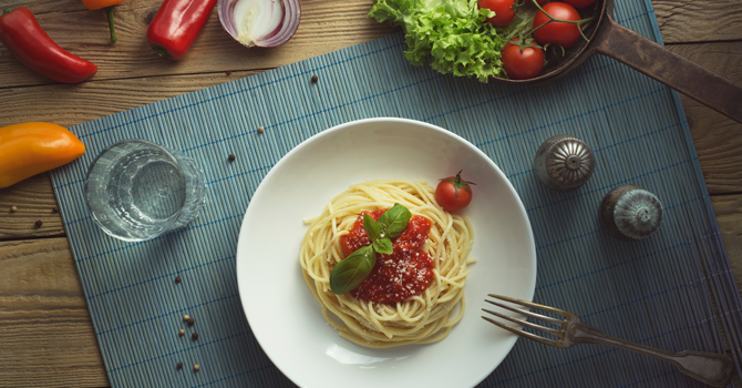 A plate of spaghetti with tomato sauce on top and vegetables on the table around it