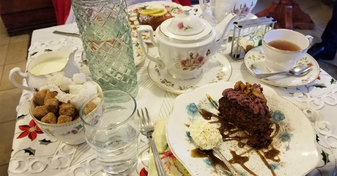 A table full of rich cakes and china teapots and cups