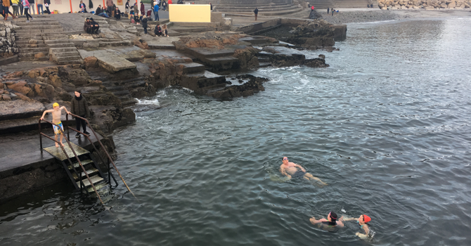 Three people swim in the sea while a boy descends a metal staircase into the water