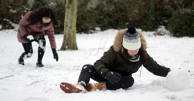 Two students playing in the snow