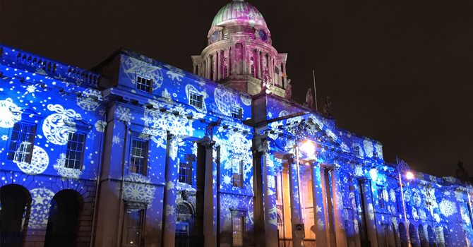A building lit up with projected patters in blue and white