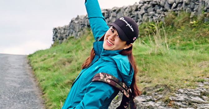 A girl with a cap and green coat smiles and poses for camera while on a walk on a grassy hillside