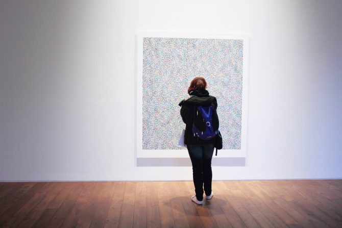Girl with backpack standing in front of a painting