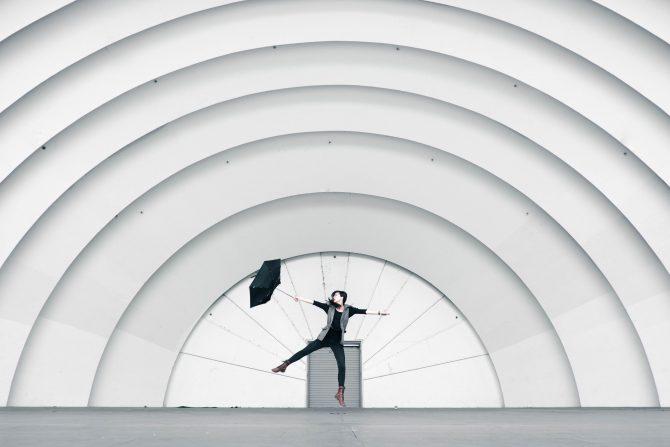 Person struggling with umbrella in white amphitheatre