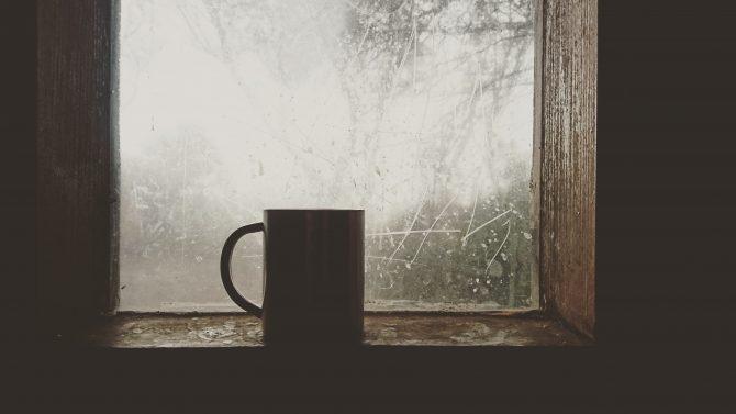 Coffee mug in dark room by a window