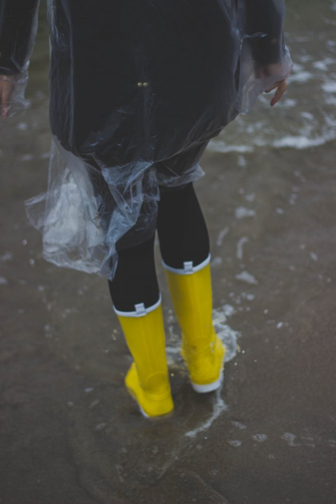 Person wearing raincoat and wellies in rain
