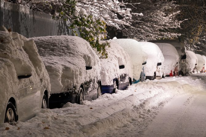 Line of cars on a road covered in a heavy blanket of snow