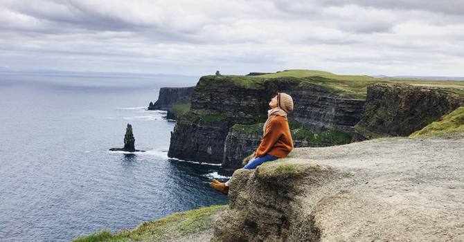 A girl sits on the cliff edge at the Cliffs of Moher