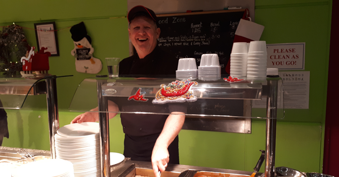 A smiling man serves lunch in a university cafeteria