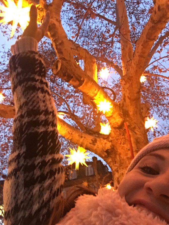 Woman in a winter coat reaching up into the branches of a tree that is covered in fairy lights