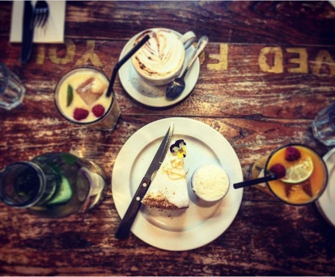 Plate of food and cup of coffee on a wooden table