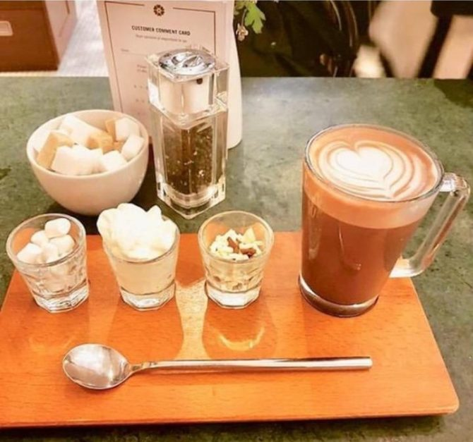 Cup opf hot chocolate with shot glasses containing cream, marshmallows and chocolate shavings