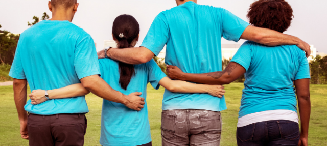 Group of four peopole in blue t shirts with arms interlinked.