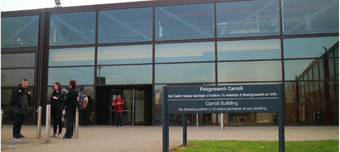Glass fronted university building, sign in front reads Carroll building
