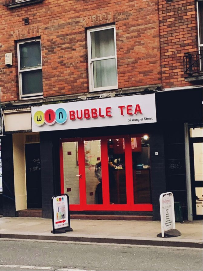 Red bricked building on Dublin street with red framed windows and a sign that reads Win Bubble Tea