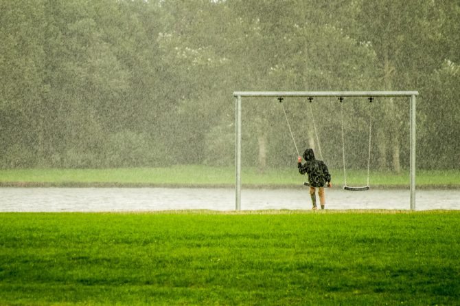 person sitting on a swing in the rain