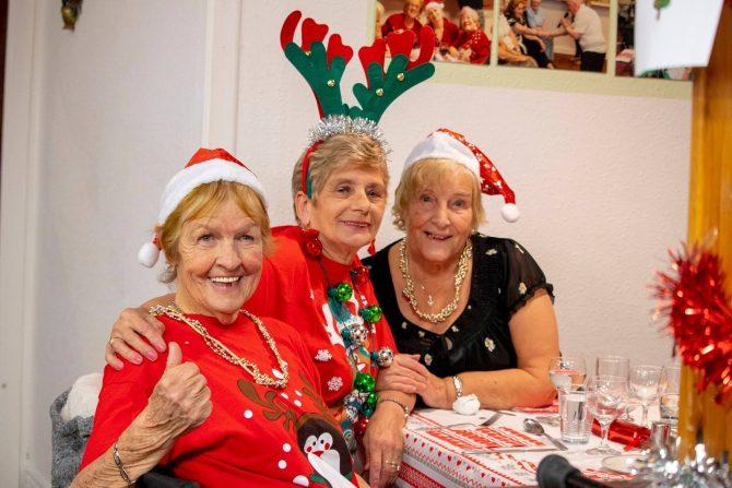 Three elderly women enjoying a christmas party in santa hats and reindeer ears