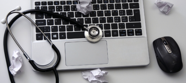 stethoscope on top of a laptop