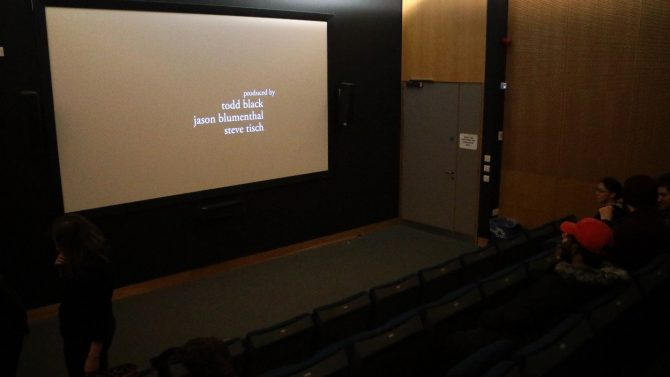 Screening room with cinema screen and rows of chairs