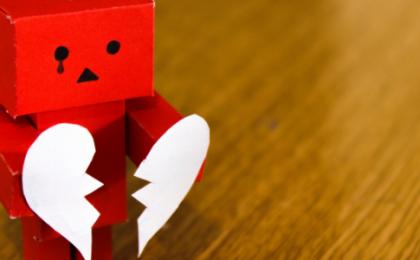 toy robot holding a broken paper heart