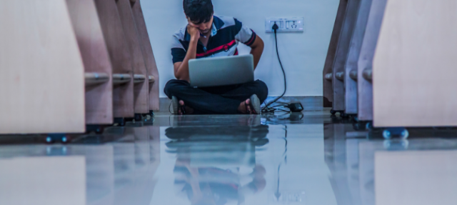 male student sitting on floor of library charging a laptop