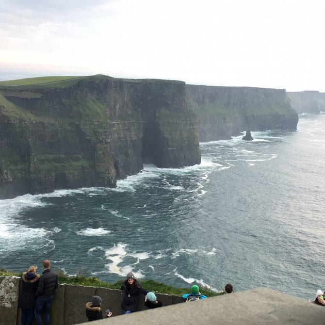 People gathered at a viewing point overlooking the cliffs of Moher and the Atlantic Ocean