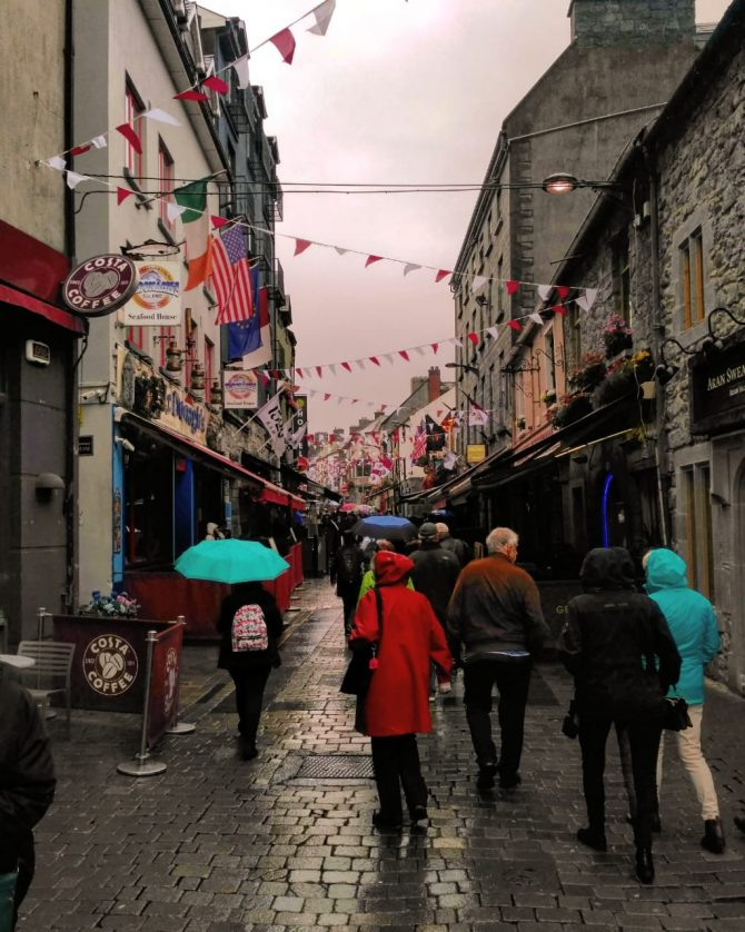 Peoplpe walking with umbrellas on a rainy cobbled side street as bunting flaps overhead