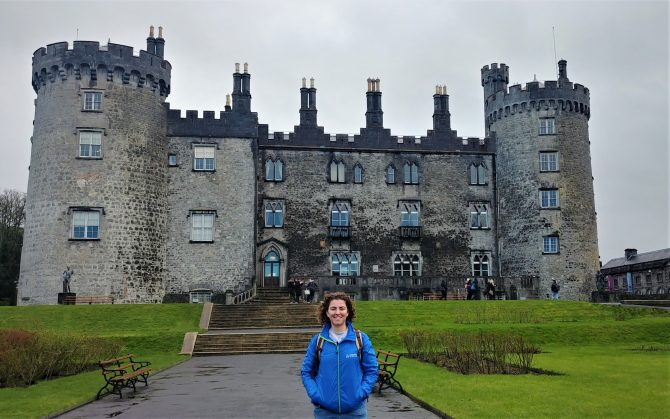 woman in blue coat standing in front of a castle