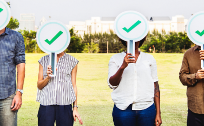 group of four people holding signs over their faces picturing a green tick of acceptance
