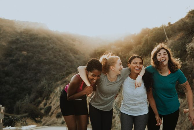 group of female friends with arms around each other smiling