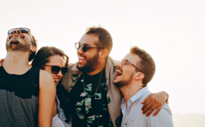 three men and a woman hugging and laughing