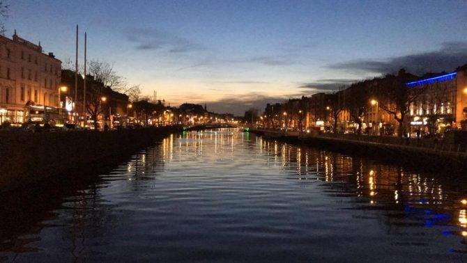 the river liffey at night time with street lights reflected on its surface