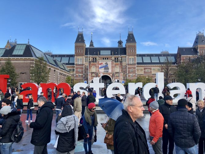 crowd gathered in front of a sign reading amsterdam in red and white
