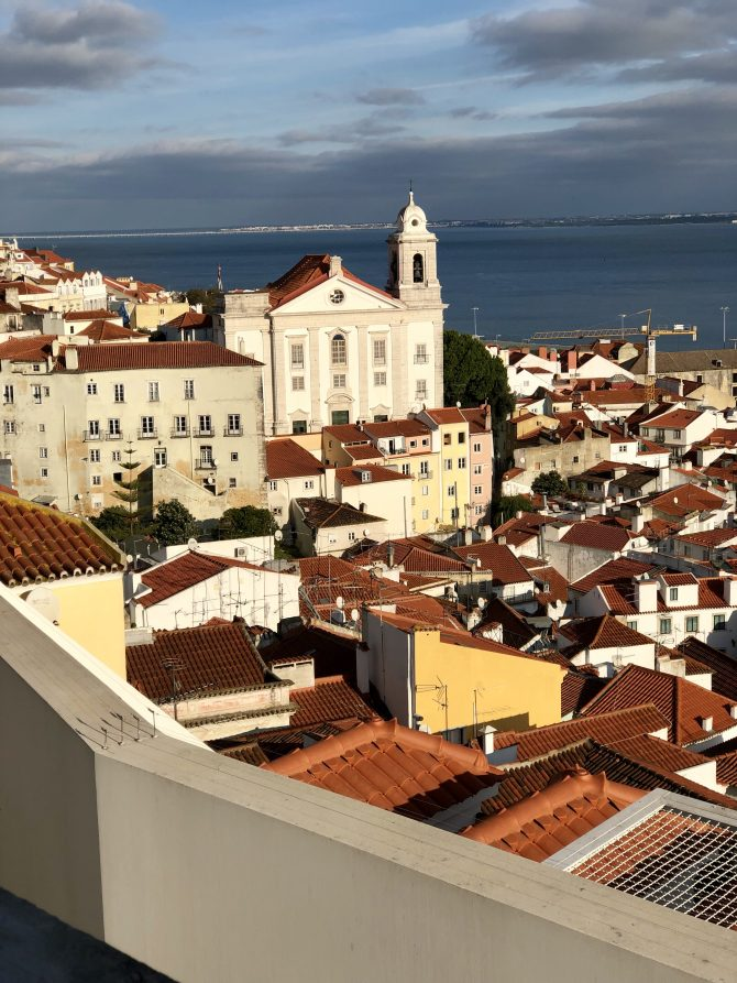 White buildings with red tiled roofs with the sea in the background
