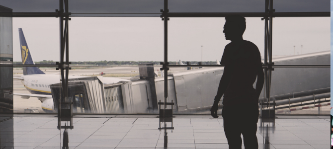 silhouette of a man in an airport with a blue and white plane in the background