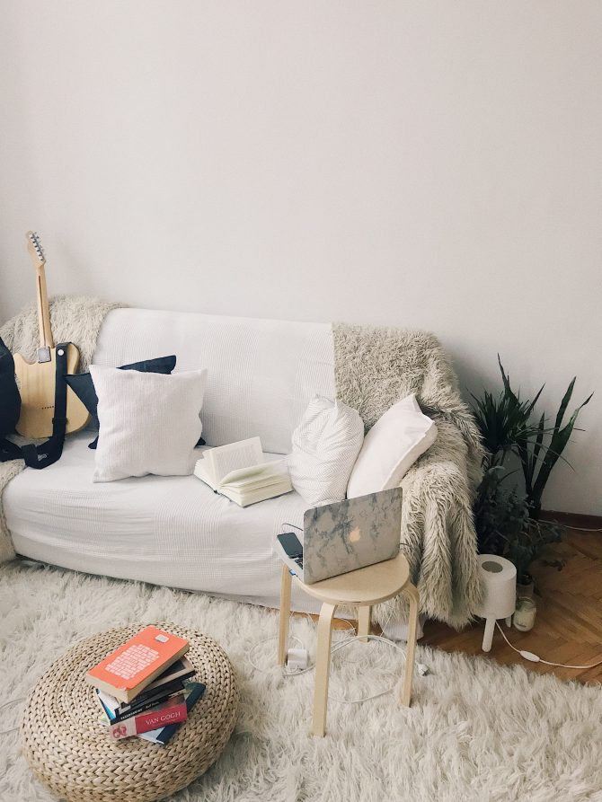 White sofa with cushions a l;aptop and books stacked up on the carpet