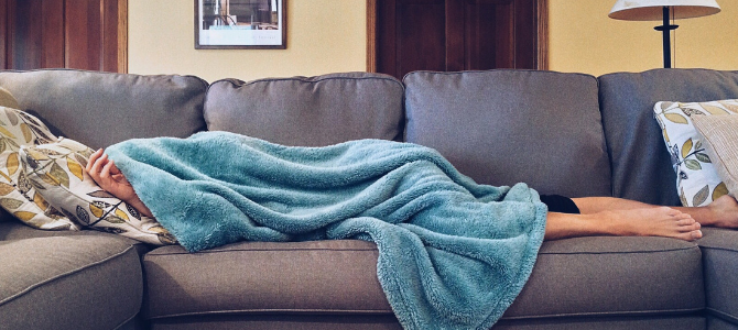 person hiding under a blue blanket on a sofa