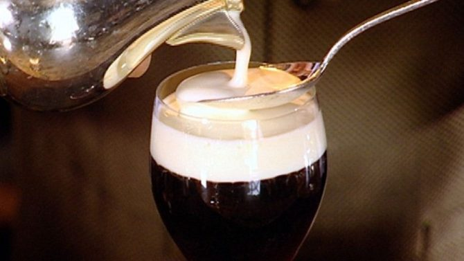 Irish coffee with cream being poured on top