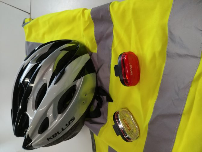 High visability jacket, bike helmet and reflected badges for the spokes of a wheel