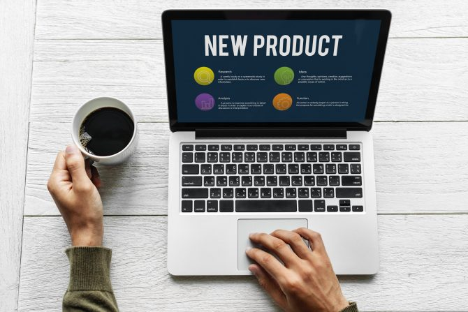 Laptop computer screen saying new product and a person holding a coffee cup