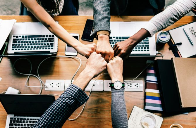 group of hands fist bumping over a desk containing computers and a power outlet