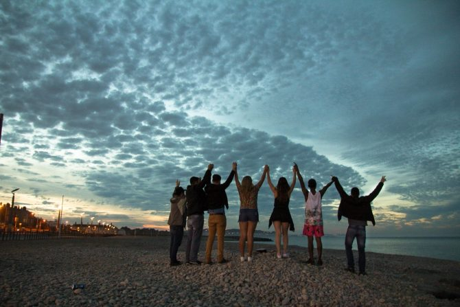group of friends standing on the shore with arms reaching up towards a cloudy sky